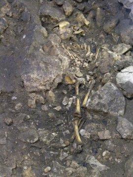 유골은 커다란 석회암들로 잘 둘러쌓여 있었고, 세 개의 돌로 아이의 머리가 조심스럽게 보호되고 있었다. 이 무덤에서는 부장품들이 여기저기서 발견되어 아이가 특별한 지위를 가지고 있었으리라는 짐작을 할 수 있다. 유골은 여러 크기의 도기 파편들이 녹색 진흙으로 덮인 것이라든지 그릇 조각, 부싯돌, 뼈로 만든 화살촉, 규암 등 여러 종류의 물건들로 덮여 있었다. Credit: Eneko Iriarte