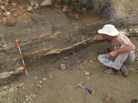 텍사스 대학 댈러스 지질과학과의 학과장이자 교수인 존 가이스만 박사가 남아프리카 카루 분지의 화산재 퇴적층을 조사하고 있다. 가이스만 박사는 2억 5천만 년 전에 있었던 지구 상에서 가장 큰 대량멸종과 관련된 지질학적 증거를 연구하는 국제연구팀의 일원이다. Credit: Photo courtesy Robert Gastaldo, Colby College